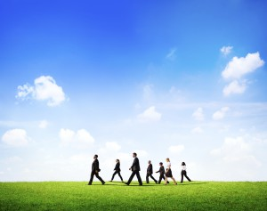 Group Of Business People Walking Through The Field In Daylight.