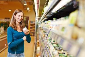 Lächelnde Frau mit Einkaufskorb kauft Milchprodukte im Supermarkt